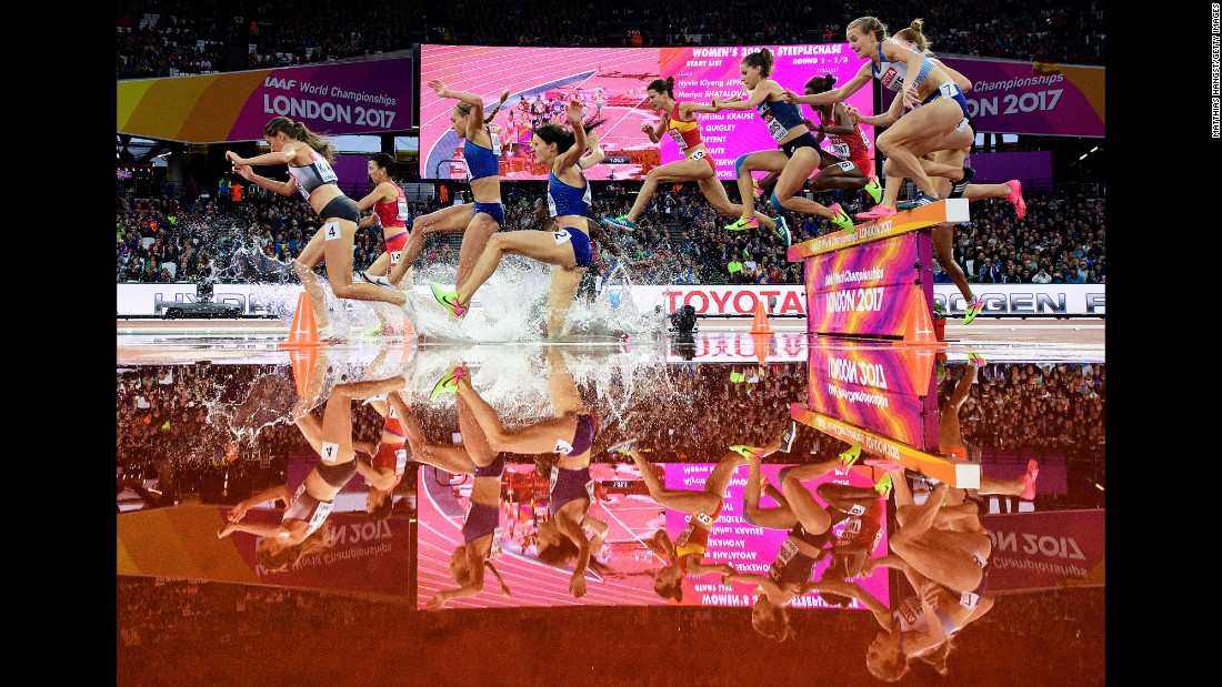 Athletes jump over a water obstacle during a steeplechase race at the World Championships on Wednesday, August 9.