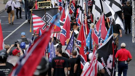 "CHARLOTTESVILLE, VA - AUGUST 12:  Hundreds of white nationalists, neo-Nazis and members of the ""alt-right"" march down East Market Street toward Emancipation Park during the ""Unite the Right"" rally August 12, 2017 in Charlottesville, Virginia. After clashes with anti-fascist protesters and police the rally was declared an unlawful gathering and people were forced out of Emancipation Park, where a statue of Confederate General Robert E. Lee is slated to be removed.  (Photo by Chip Somodevilla/Getty Images)"