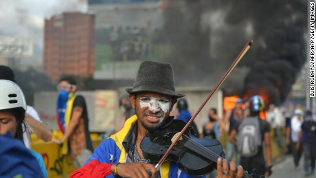 TOpposition activist Wuilly Arteaga plays the violin during a protest against President Nicolas Maduro in Caracas on May 27, 2017.  Demonstrations that got underway in late March have claimed the lives of 58 people, as opposition leaders seek to ramp up pressure on Venezuela's leftist president, whose already-low popularity has cratered amid ongoing shortages of food and medicines, among other economic woes. / AFP PHOTO / LUIS ROBAYO        (Photo credit should read LUIS ROBAYO/AFP/Getty Images)