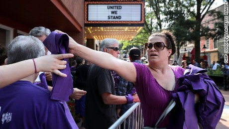 Anna Quillon hands out purple pieces of purple cloth outside Heather Heyer's memorial service on Wednesday. Purple was a favorite color of Heyer's.