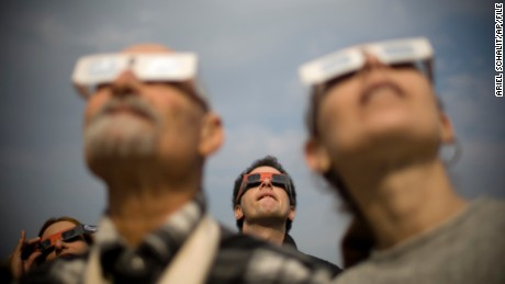 Israelis watch at a partial solar eclipse in the town of Givatayim near Tel Aviv, Israel, Tuesday, Jan. 4, 2011. A partial solar eclipse began Tuesday in the skies over the Mideast and will extend across much of Europe. (AP Photo/Ariel Schalit)