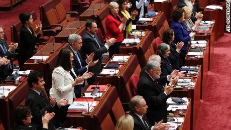 Members of the Senate stand and applaud Attorney-General George Brandis after the exchange.