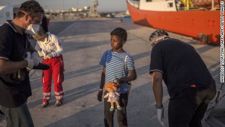 A child, who was aboard the Aquarius rescue ship, receives flip-flops upon her arrival in the port of Pozzallo, Italy, in August 2017.