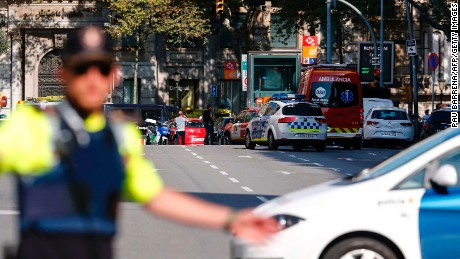 A policemen stand as he blocks the street to a cordoned off area after a van ploughed into the crowd, injuring several persons on the Rambla in Barcelona on August 17, 2017. / AFP PHOTO / PAU BARRENA        (Photo credit should read PAU BARRENA/AFP/Getty Images)