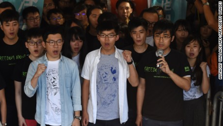 Nathan Law (L), Joshua Wong (C) and Alex Chow, leaders of Hong Kong's 'Umbrella Movement', gesture as they address the media before their sentencing in Hong Kong on August 17, 2017. Wong, Law and Chow were found guilty last year on unlawful assembly charges for storming a government forecourt as part of an anti-Beijing protest in 2014. / AFP PHOTO / Anthony WALLACE        (Photo credit should read ANTHONY WALLACE/AFP/Getty Images)