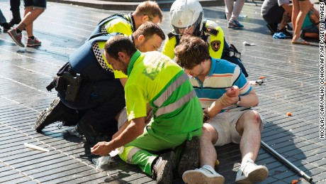 "A person is helped by Spanish policemen and two men after a van ploughed into the crowd, killing at least 13 people and injuring around 100 others on the Rambla in Barcelona on August 17, 2017. A driver deliberately rammed a van into a crowd on Barcelona's most popular street on August 17, 2017 killing at least 13 people before fleeing to a nearby bar, police said.  Officers in Spain's second-largest city said the ramming on Las Ramblas was a ""terrorist attack"". The driver of a van that mowed into a packed street in Barcelona is still on the run, Spanish police said. / AFP PHOTO / Nicolas CARVALHO OCHOA        (Photo credit should read NICOLAS CARVALHO OCHOA/AFP/Getty Images)"