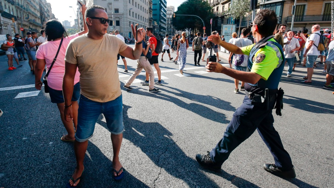 A police officer asks people to move back in Barcelona.