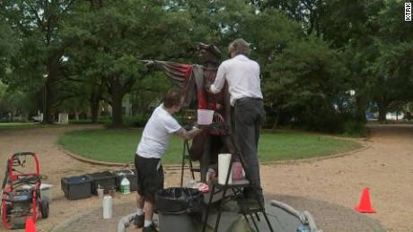 Men cleaning the statue after it was vandalized.