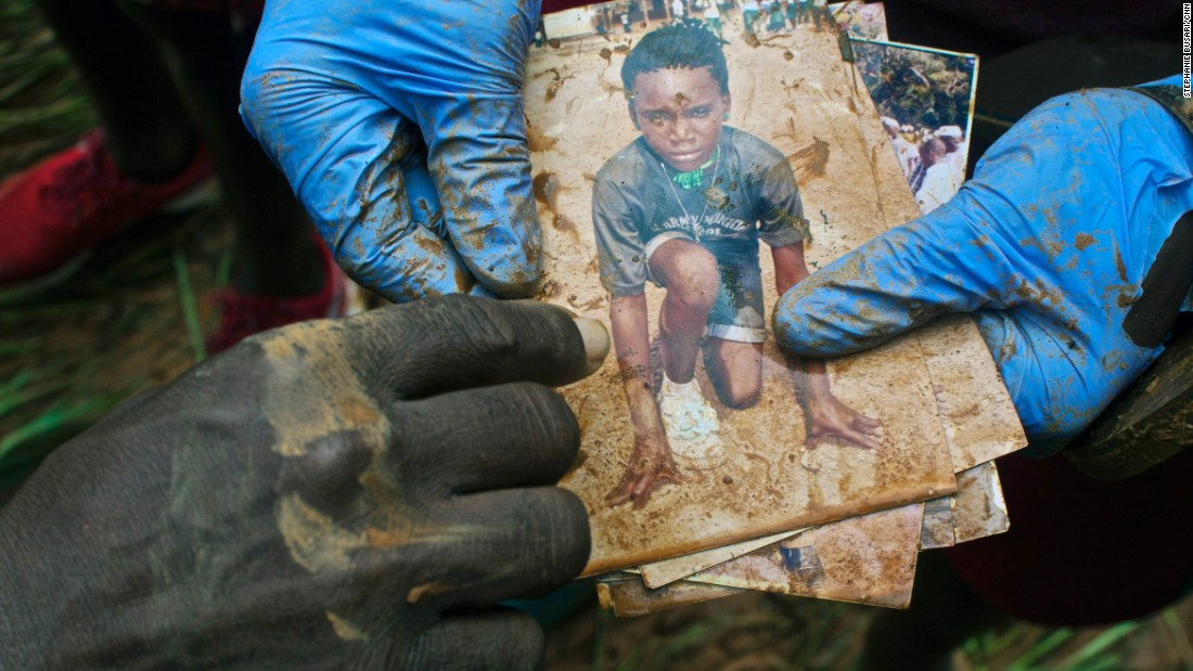 Family photographs are recovered from a mudslide victim on August 17, in the Lumley mangrove of Freetown, Sierra Leone. Sources at the scene confirmed that the body of the young boy in this photo was recovered.