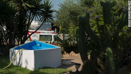 An ambulance is seen through a neighbor's front lawn, where a hose dangles in a half-empty pool.
