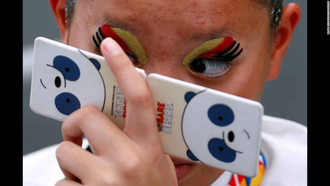 A synchronized swimmer from Thailand checks her makeup before competing in the Southeast Asian Games on Sunday, August 20.