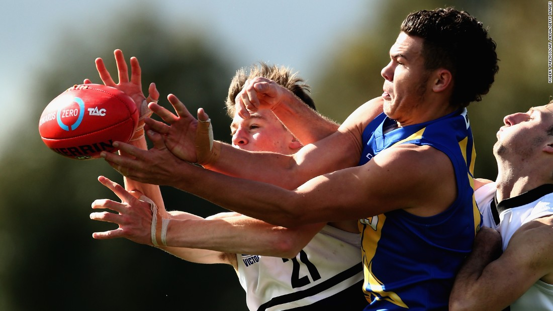 Players reach for the ball during an Australian rules football match in Melbourne on Saturday, August 19.