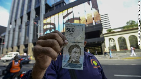 A man shows a new 500-Bolivar-note (74 cents of US dollar) in Caracas on January 16, 2017. A new family of currency will progressively come into circulation in the South American country that has the highest inflation rate in the world, which IMF forecasts say could soon hit 475 percent. / AFP PHOTO / JUAN BARRETO        (Photo credit should read JUAN BARRETO/AFP/Getty Images)