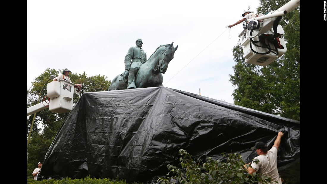 "City workers in Charlottesville, Virginia, <a href=""http://www.cnn.com/2017/08/23/us/charlottesville-monument-cover-fabric-trnd/index.html"" target=""_blank"">drape a tarp</a> over a statue of Confederate Gen. Robert E. Lee on Wednesday, August 23. The statue was one of two monuments that were the focus of violent protests in Charlottesville earlier this month."