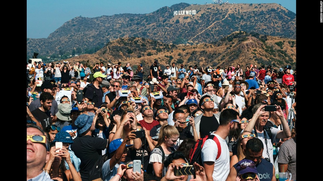 A crowd gathers in front of the iconic Hollywood sign to watch the solar eclipse Monday, August 21, at the Griffith Observatory in Los Angeles.