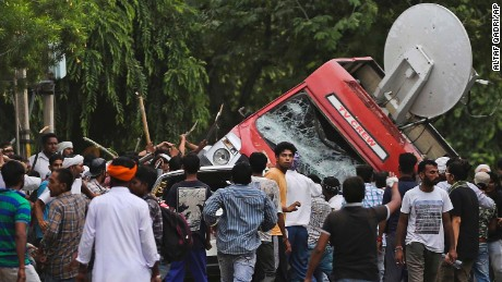 Followers of Gurmeet Ram Rahim Singh overturn a satellite van Friday in Panchkula, India.