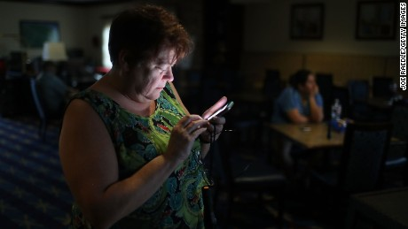 Amy Currin watches the weather news on her cell phone after the power went out at the TownePlace Suites hotel where she was taking shelter from Hurricane Harvey at a place she felt was safer than her home on August 25, 2017 in Corpus Christi, Texas.  Hurricane Harvey has intensified into a hurricane and is aiming for the Texas coast with the potential for up to 3 feet of rain and 125 mph winds.