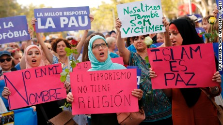 "Muslim women hold placards reading ""Not in my name,"" ""Terrorism doesn't have a religion"" and ""Islam is Peace."""