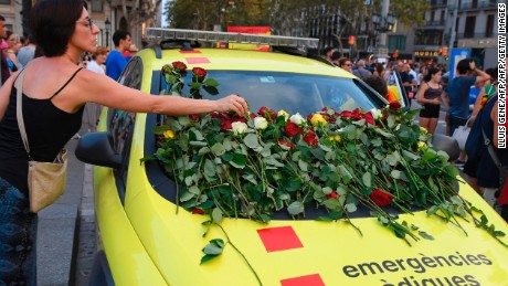A woman places roses on an ambulance vehicle in Barcelona on Saturday.