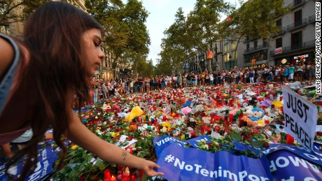 "A woman places a placard reading ""We are not afraid"" at the Las Ramblas promenade on Saturday."