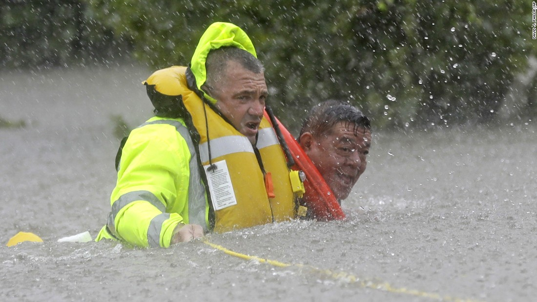 Wilford Martinez, right, is rescued from his flooded car along Interstate 610 in Houston on August 27. Assisting him here is Richard Wagner of the Harris County Sheriff's Department.