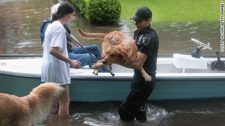 Volunteers and officers from a neighborhood security patrol help rescue residents and their dogs in the River Oaks neighborhood after it was inundated with flooding on August 27, 2017 in Houston.