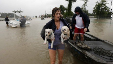 Belinda Penn holds her dogs Winston and Baxter after being rescued from their home as floodwaters from Tropical Storm Harvey rise Monday, Aug. 28, 2017, in Spring, Texas.