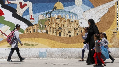 Palestinians walk past a mural in Gaza in 2014 featuring Handala, Naji al-Ali's most famous character, holding the key to the city of Jerusalem.