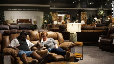 David and Maria Parks sit on a couch in the Gallery Furniture showroom, watching local news coverage of the floods.
