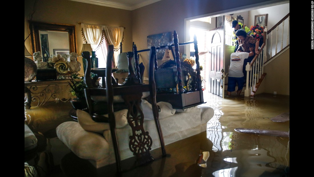 Chris Gutierrez, second from right, helps his grandmother, Edelmira Gutierrez, down the stairs of their flooded house and into a waiting firetruck in the Concord Bridge neighborhood of Houston on August 29.