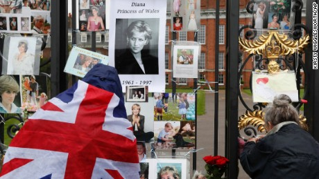 Royal well-wishers look at and attach pictorial tributes to the late Princess Diana on the gates outside of Kensington Palace in London, Wednesday, Aug. 30, 2017. Princes William and Harry are paying tribute to their mother, Princess Diana, on the eve of the 20th anniversary of her death by visiting the Sunken Garden to honor Diana's work with charities. (AP Photo/Kirsty Wigglesworth)