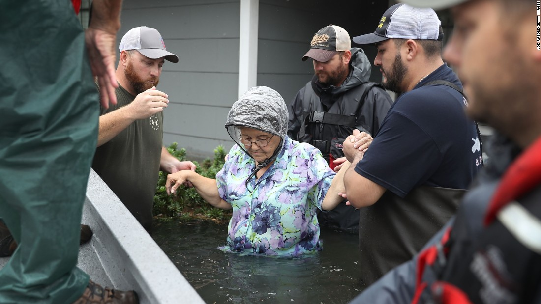 Volunteer rescue workers help a woman from her flooded home in Port Arthur on August 30.