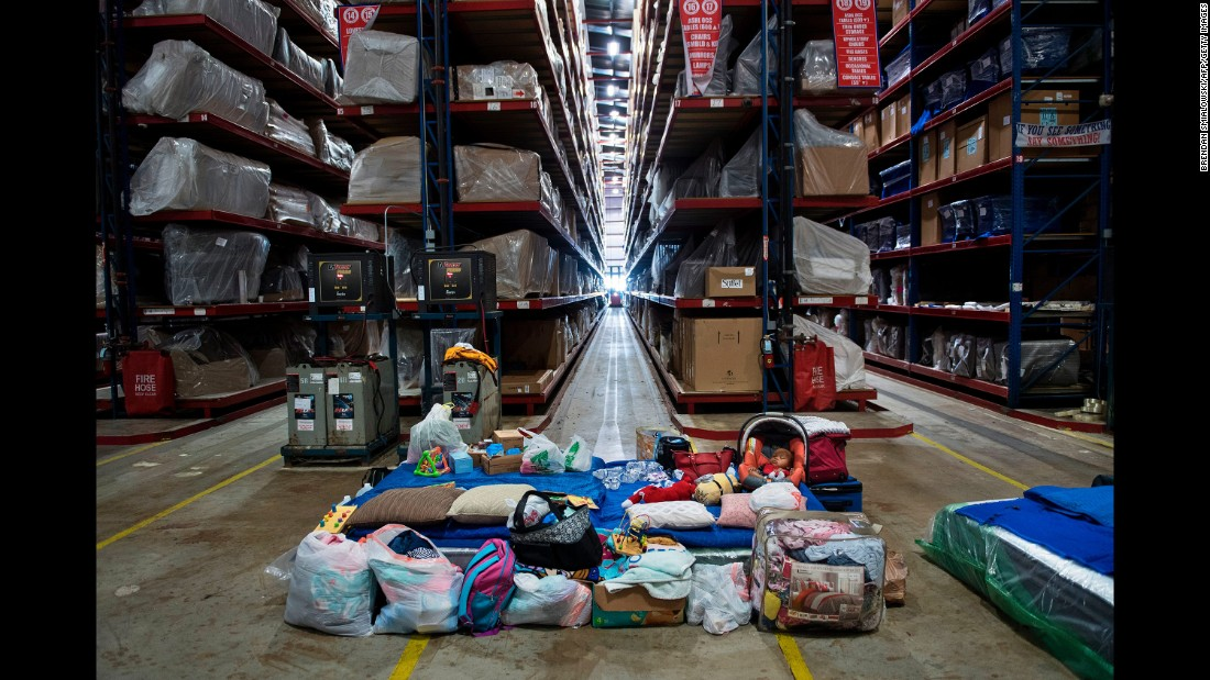 "A baby sits with family belongings at a<a href=""http://www.cnn.com/2017/08/30/us/gallery-furniture-store-houston-shelter/index.html""> Gallery Furniture store</a> in Houston  being used as a temporary shelter on August 30."