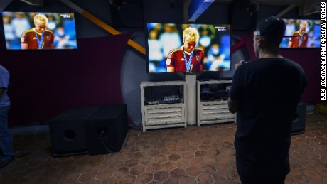 A Venezuela fan watches on TV after his team loses to England in the U-20 World Cup final football match on June 11, 2017, in Caracas, Venezuela. / AFP PHOTO / LUIS ROBAYO        (Photo credit should read LUIS ROBAYO/AFP/Getty Images)