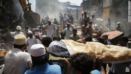 The body of a victim is carried out from the site of a building collapse in Mumbai, India, Thursday, Aug. 31, 2017. (AP Photo/Rafiq Maqbool)