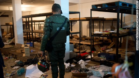 A member of the Venezuelan National Guard looks at the debris left in a looted supermarket in Ciudad Bolivar, Venezuela, on December 19, 2016.