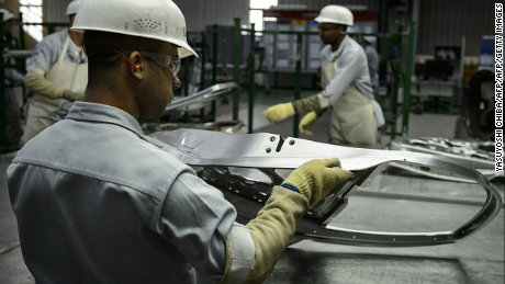 Workers check stamped parts at the production area of the March and Versa models at Nissan's Industrial Complex in Resende, 160 km west of Rio de Janeiro, Brazil, on Februrary 3, 2015. The Nissan plant in Brazil will be able to produce 200,000 cars and utility vehicles per year. The company aims to achieve 5 percent of the market share by 2016 in Brazil, the fourth largest automotive market in the world. AFP PHOTO / YASUYOSHI CHIBA        (Photo credit should read YASUYOSHI CHIBA/AFP/Getty Images)