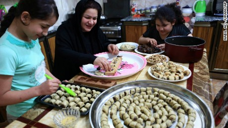 An Iraqi mother and her children prepare cookies for the upcoming Muslim Eid al-Adha holiday in Basra, Iraq on Thursday.
