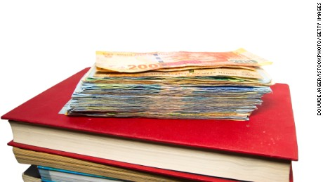 Knowledge equals money with a stack of South-African banknotes on a pile of books on white