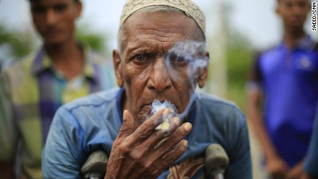 An elderly Rohingya man smokes the last of his Burmese cigar while looking for shelter in Bangladesh with his family near Kutupalang unregistered camp.