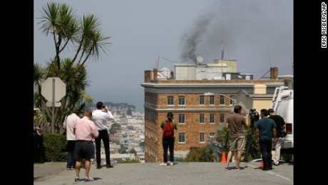 People stop to watch black smoke coming from the Russian Consulate's roof Friday in San Francisco.