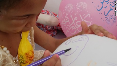 Buthaina draws on a balloon brought to her by one of her visitors.