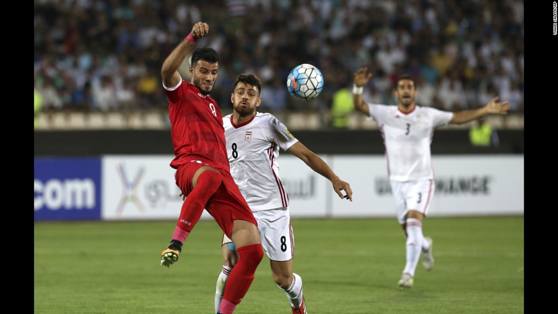 Syria's Omar Al Somah, left, fends off Iran's Morteza Pouraliganji during Tuesday's qualifier. Al Somah scored the game-tying goal late in stoppage time.