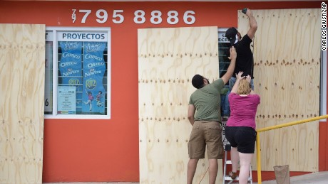 CORRECTS CITY - Cyber School Supply Christopher Rodriguez is supported as he installs wood panels over a storefront window in preparation for Hurricane Irma, in Toa Baja, Puerto Rico, Tuesday, Sept. 5, 2017. Irma grew into a dangerous Category 5 storm, the most powerful seen in the Atlantic in over a decade, and roared toward islands in the northeast Caribbean Tuesday. (AP Photo/Carlos Giusti)