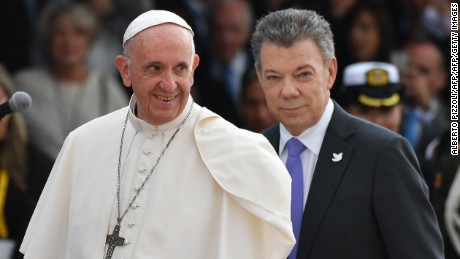 "Pope Francis (C) is welcomed by Colombia President Juan Manuel Santos (R) and his wife Maria Clemencia upon landing in Bogota on September 6, 2017.  Pope Francis arrived in Colombia for a five-day tour to plead for a ""stable and lasting"" peace in a divided country just emerging from a 50-year war that claimed hundreds of thousands of lives. / AFP PHOTO / Alberto PIZZOLI        (Photo credit should read ALBERTO PIZZOLI/AFP/Getty Images)"