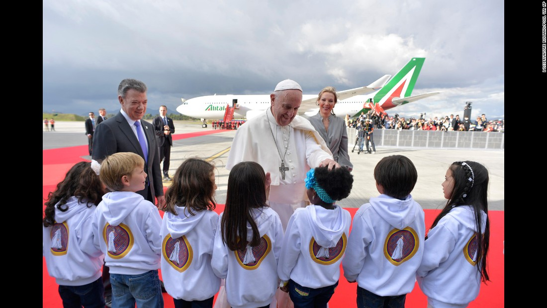 Francis, here with Colombian President Juan Manuel Santos and first lady Maria Clemencia Rodriguez, greets children during a welcoming ceremony September 6 at El Dorado International Airport in Bogota.