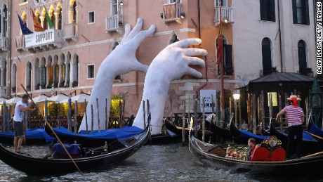 VENICE, ITALY - MAY 19:  The sculpture 'Support' by Italian artist Lorenzo Quinn is seen in Venice, Italy, on May 19, 2017. The artwork, featuring two hands holding up the Ca' Sagredo Hotel, is part of the the 57th International Art Exhibition of the Venice Biennale, and is intended to highlight climate change.  (Photo by Adam Berry/Getty Images)