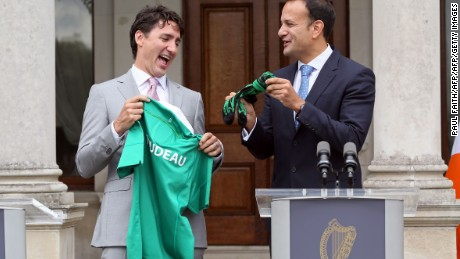 Canada's Prime Minister Justin Trudeau (L) is presented with an Ireland rugby union shirt and a pair of socks, by Ireland's Prime Minister Leo Varadkar (R) at Farmleigh House in Dublin on July 4, 2017.