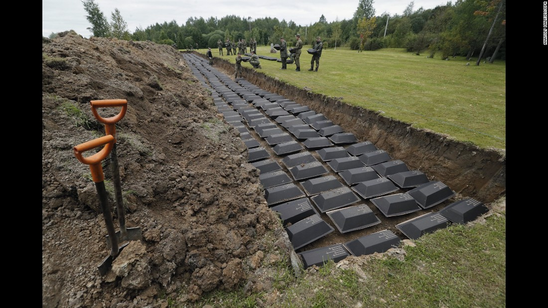 German and Russian soldiers take part in a reburial ceremony Wednesday, September 6, for hundreds of German soldiers who were killed during World War II. The remains were found in Russia's Leningrad region and reburied at a cemetery in Sologubovka, Russia.