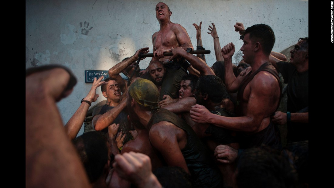 People covered in black grease climb on one another Wednesday, September 6, during the Cascamorras festival in Baza, Spain.
